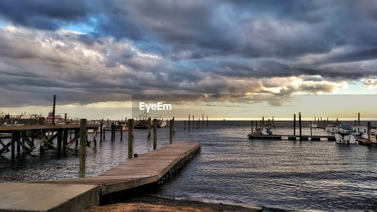Piers On Sea Against Cloudy Sky During Sunset