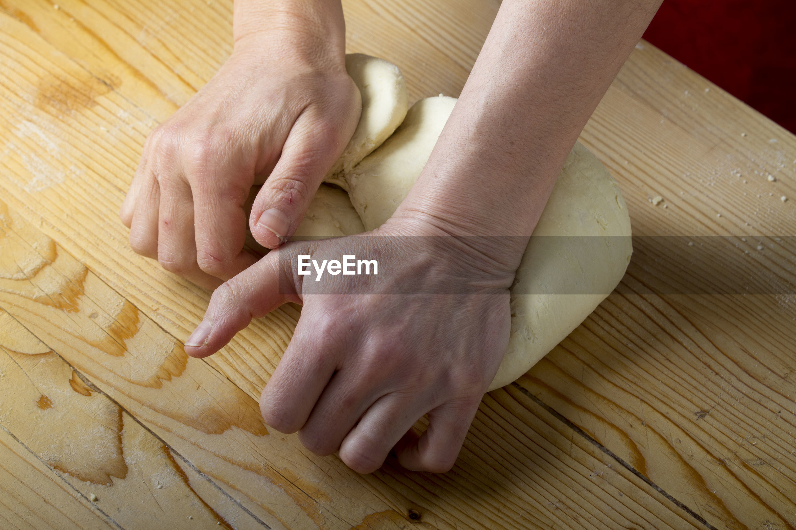 Cropped hands preparing pasta dough on table