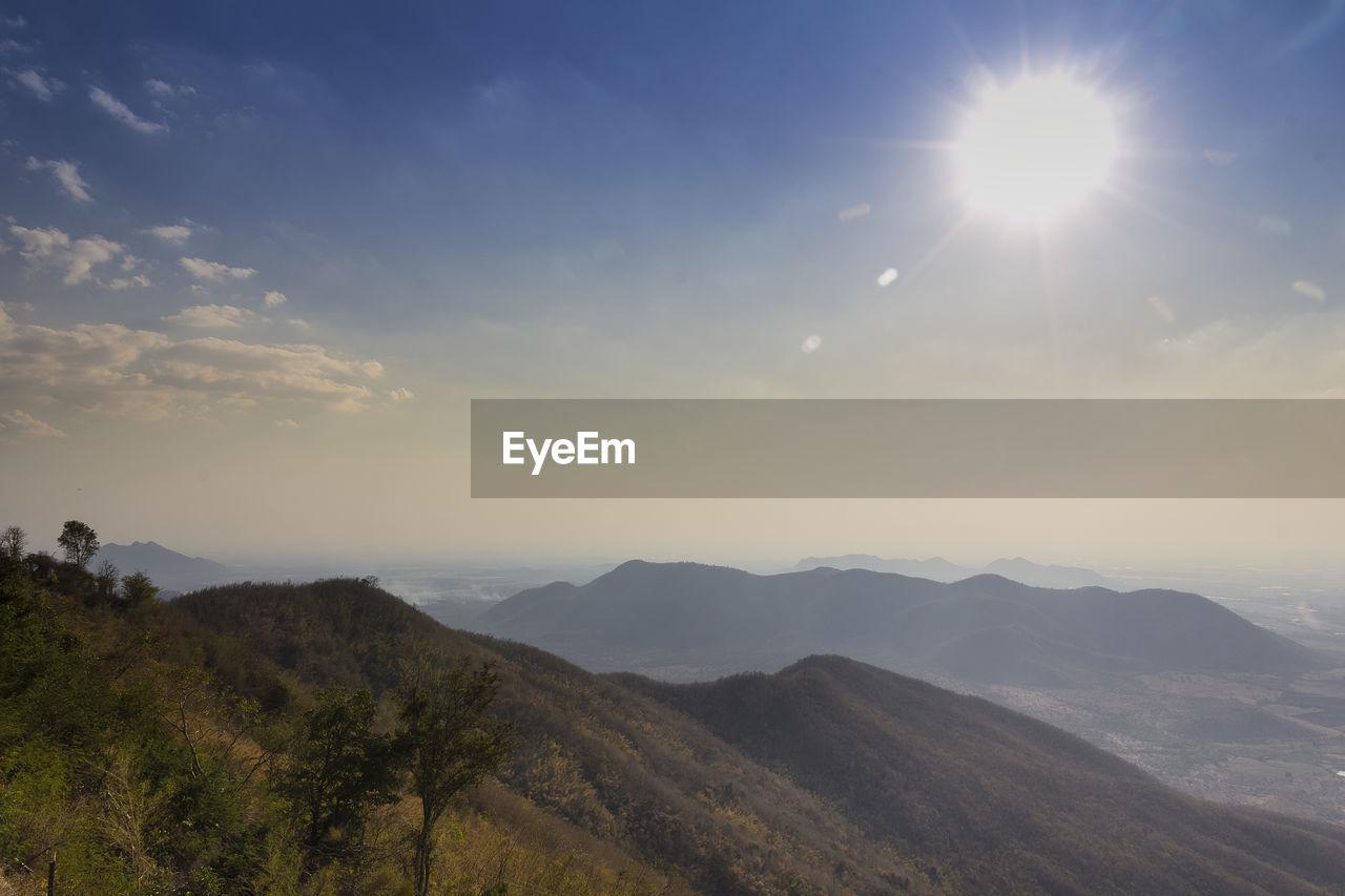 sky, mountain, beauty in nature, scenics - nature, tranquility, tranquil scene, sunlight, non-urban scene, nature, cloud - sky, mountain range, idyllic, landscape, environment, sun, no people, outdoors, sunbeam, day, lens flare, bright, mountain peak
