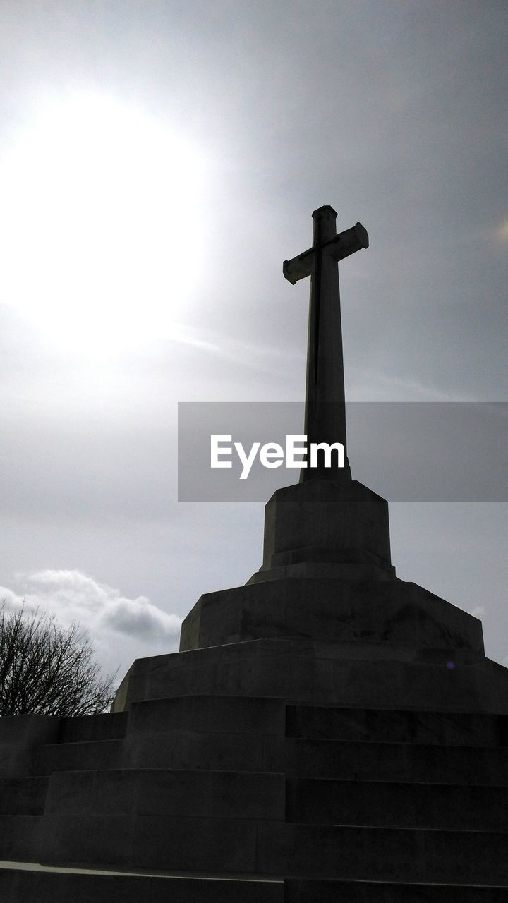 Low Angle View Of Cross In Cemetery On Sunny Day