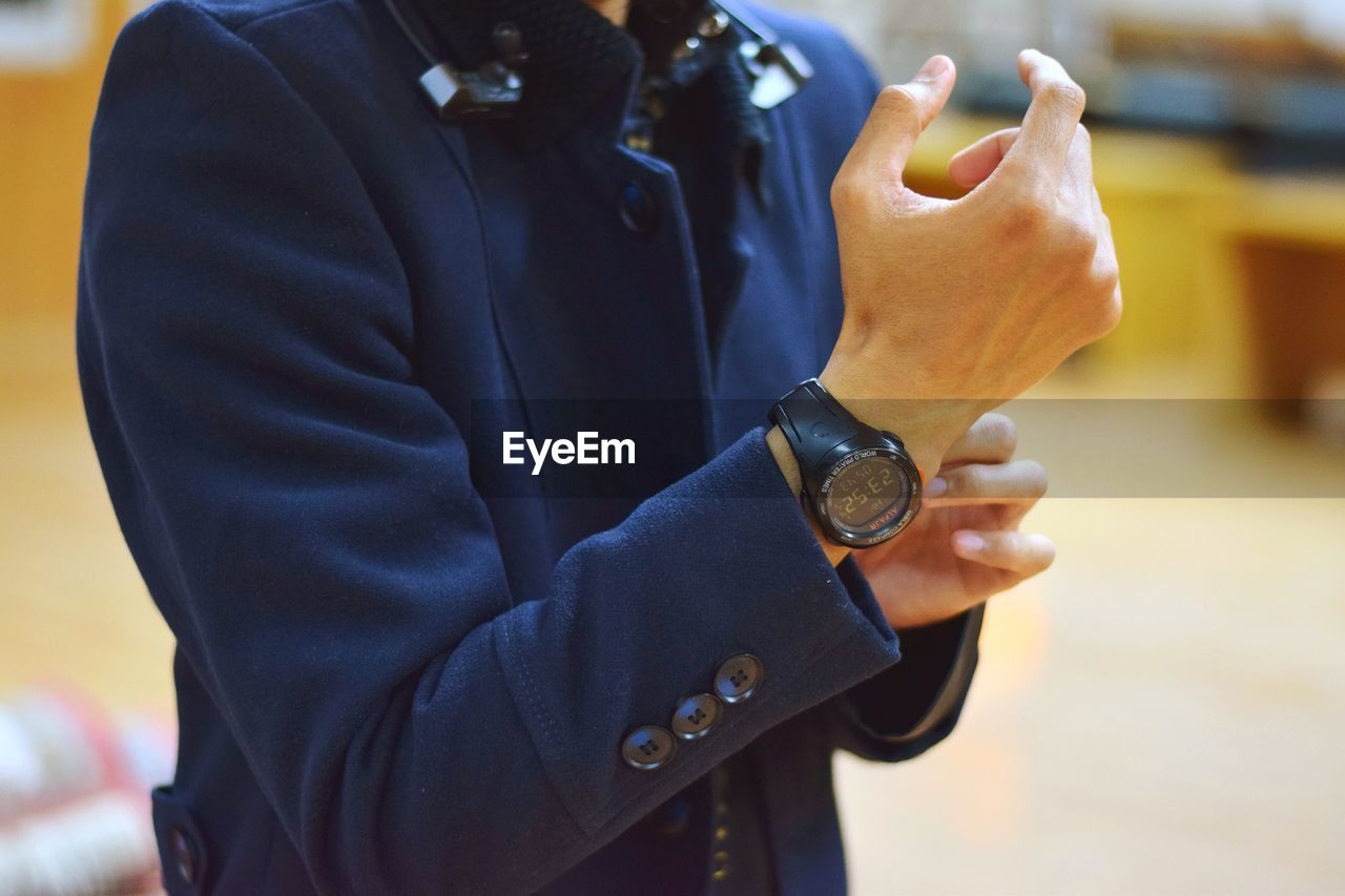 midsection, one person, focus on foreground, holding, real people, hand, human hand, lifestyles, women, standing, business, human body part, close-up, men, adult, day, indoors, time, wristwatch, finger