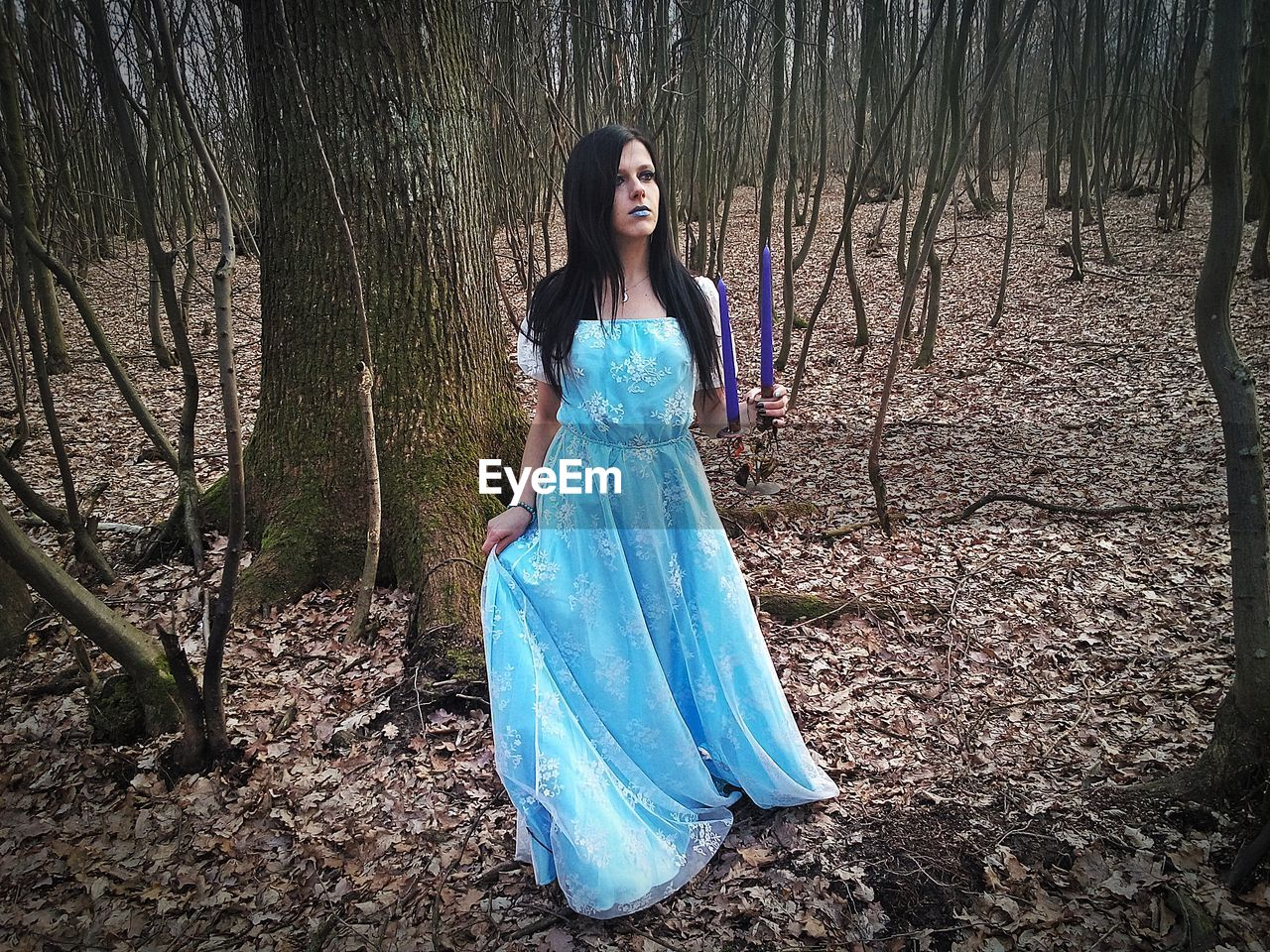 Woman wearing dress and holding candles while standing amidst trees at forest