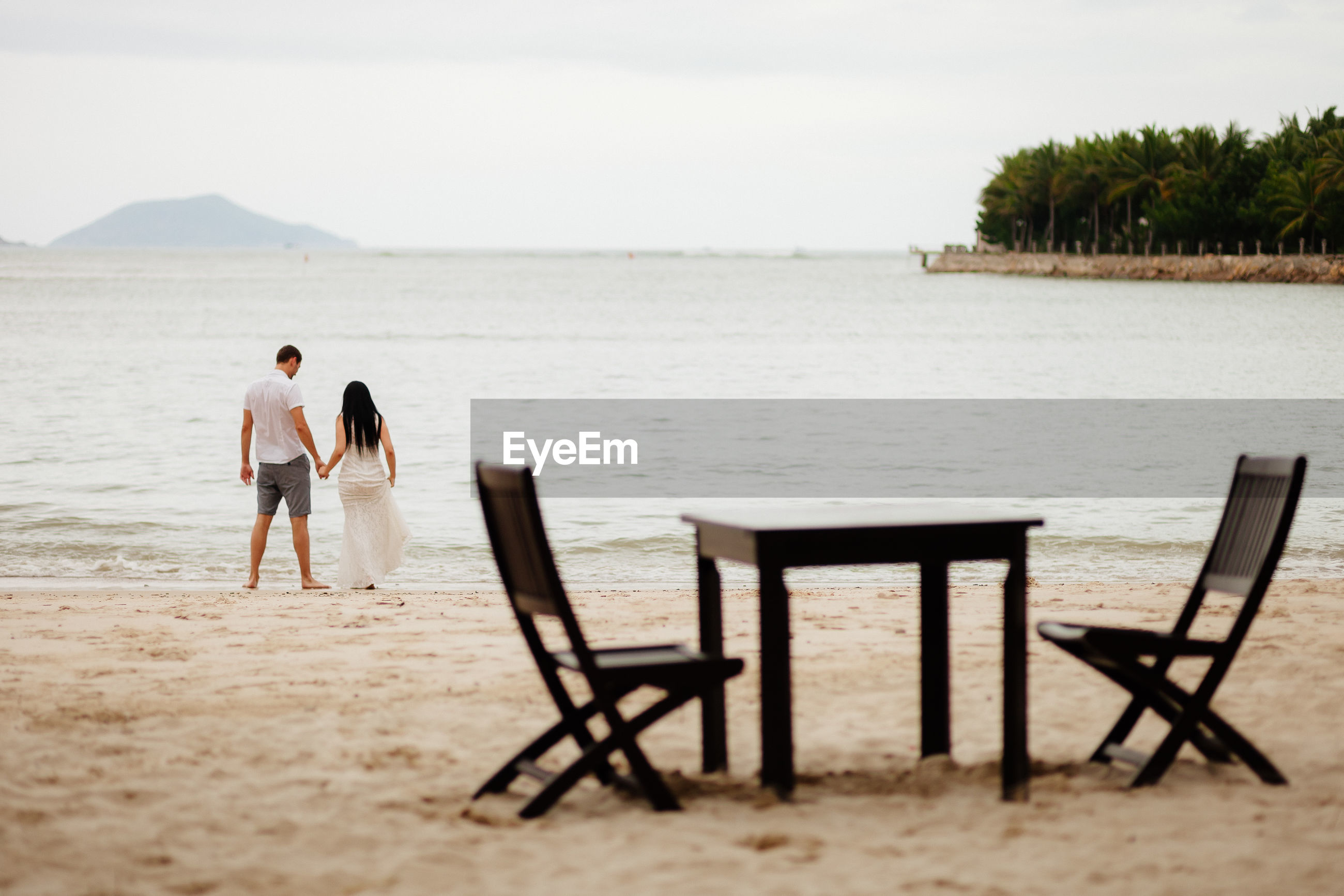 Rear view of couple at beach with table and chairs in foreground