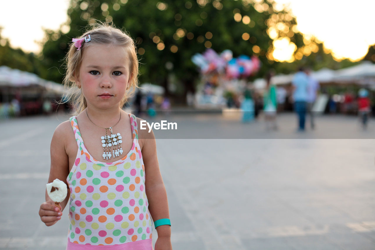 Portrait Of Cute Girl Holding Ice Cream While Standing Outdoors