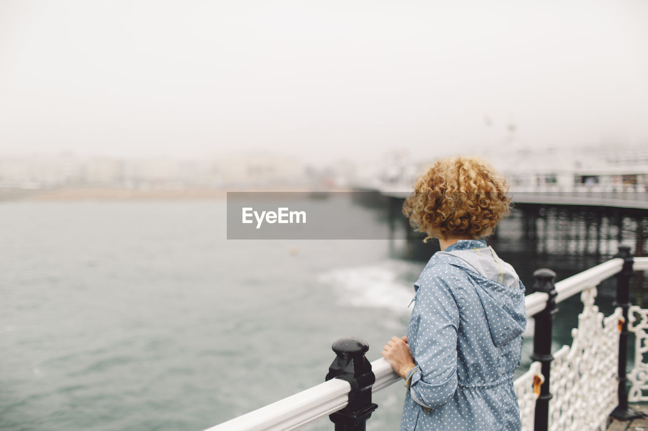 Rear View Of Young Woman Standing By Railing On Brighton Pier