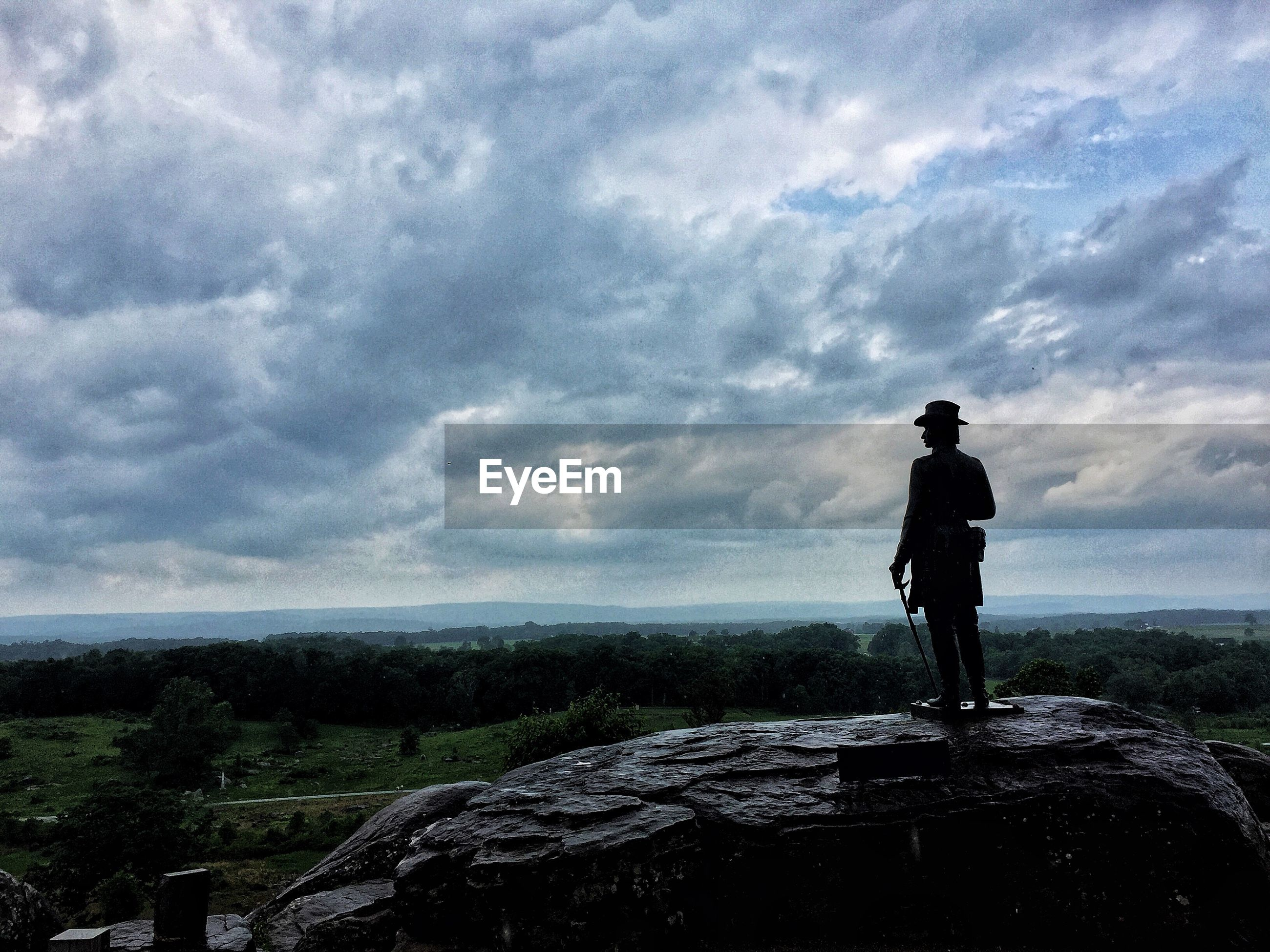 MAN STANDING ON ROCK LOOKING AT VIEW OF SKY