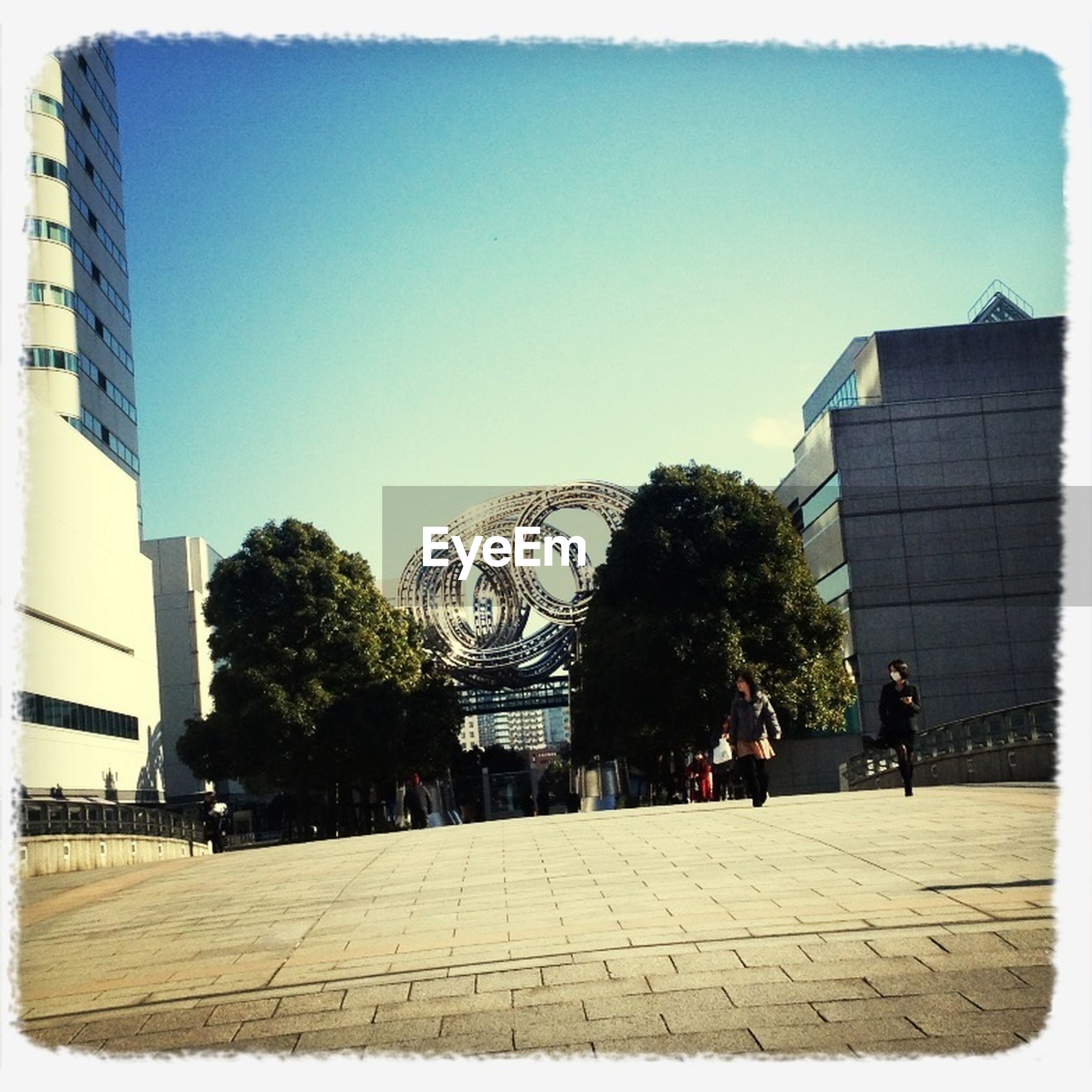 transfer print, building exterior, architecture, clear sky, built structure, tree, auto post production filter, city, copy space, blue, sunlight, footpath, the way forward, incidental people, outdoors, day, shadow, men, walking