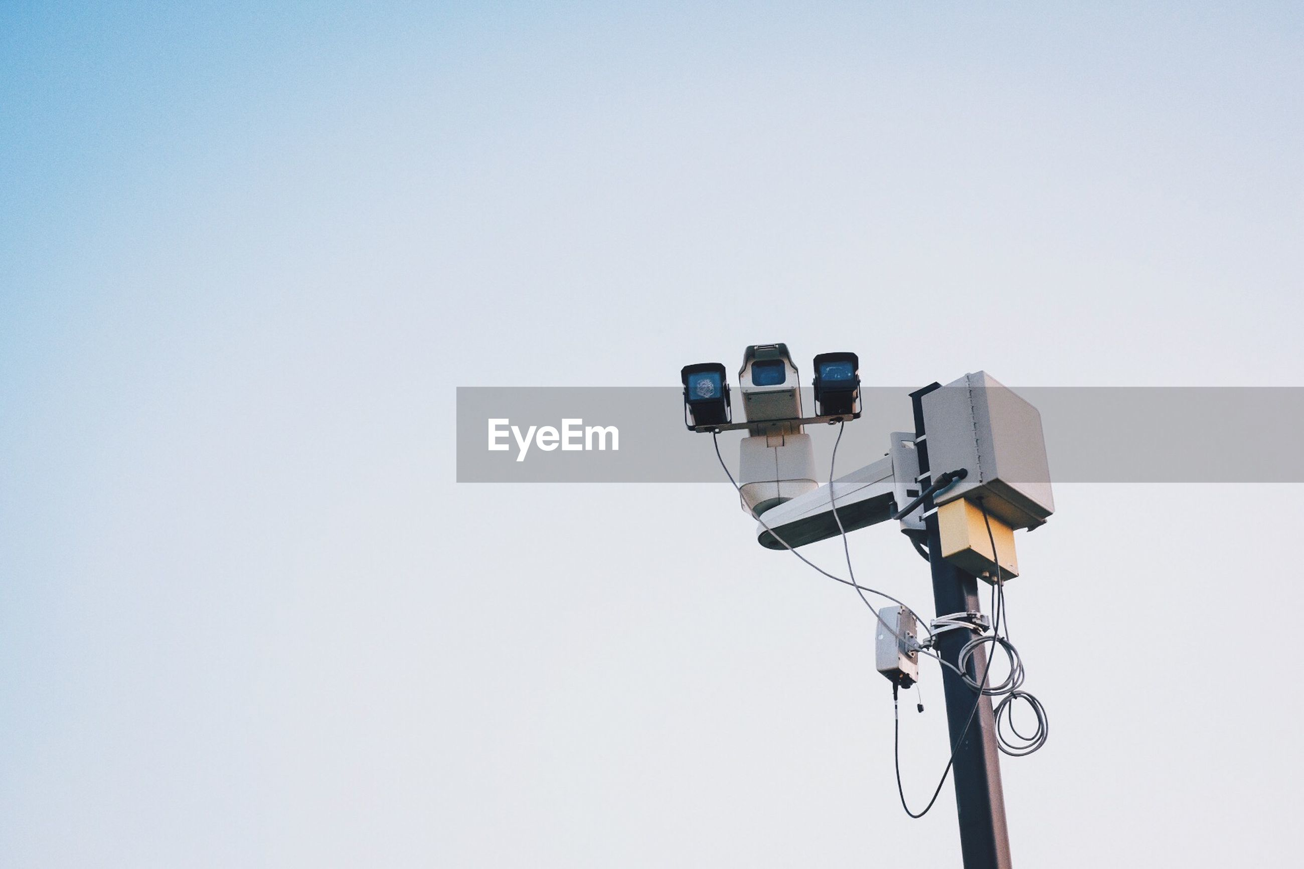 Low angle view of security camera on street light against clear sky