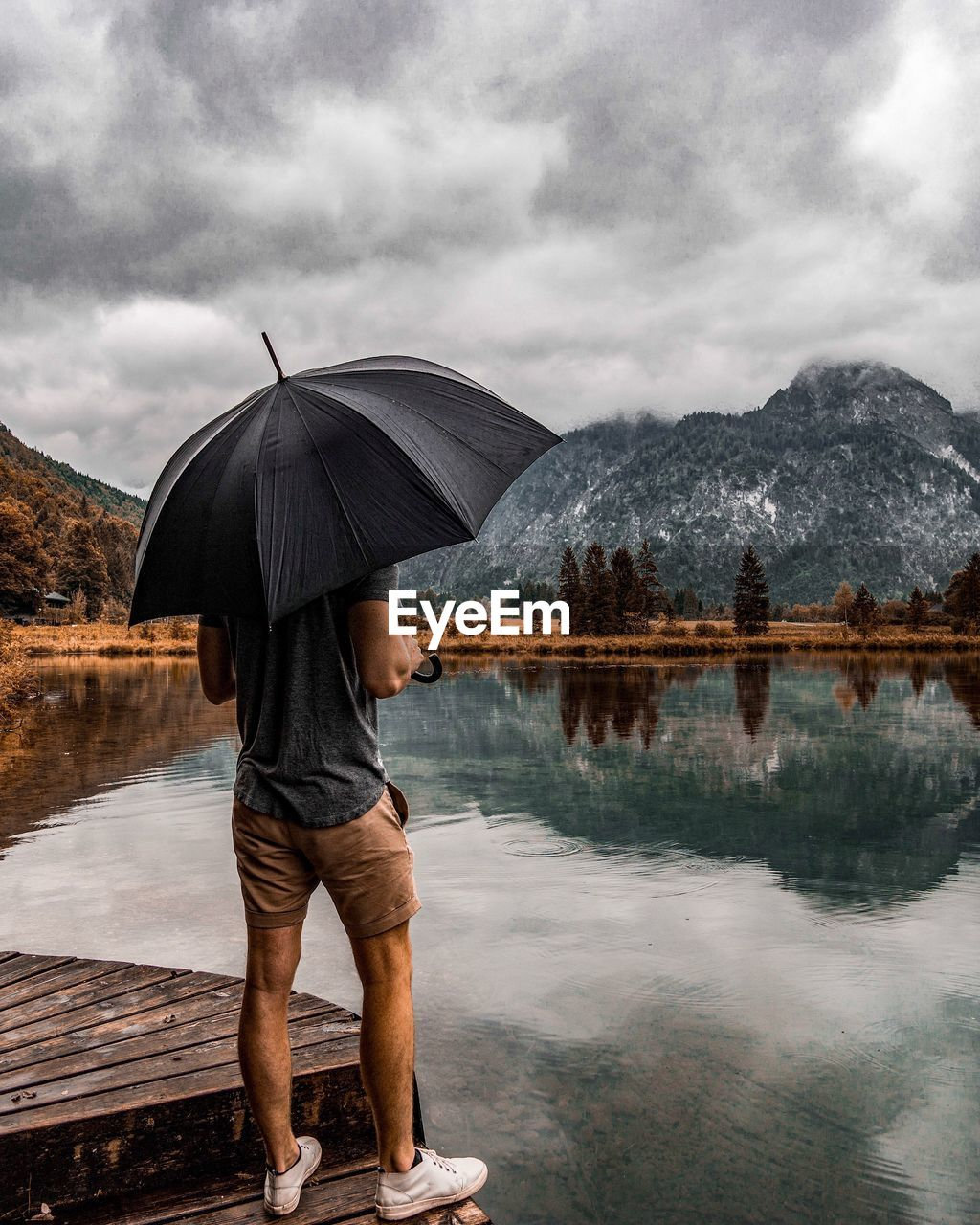 Rear View Of Man With Umbrella Standing By Lake With Reflection
