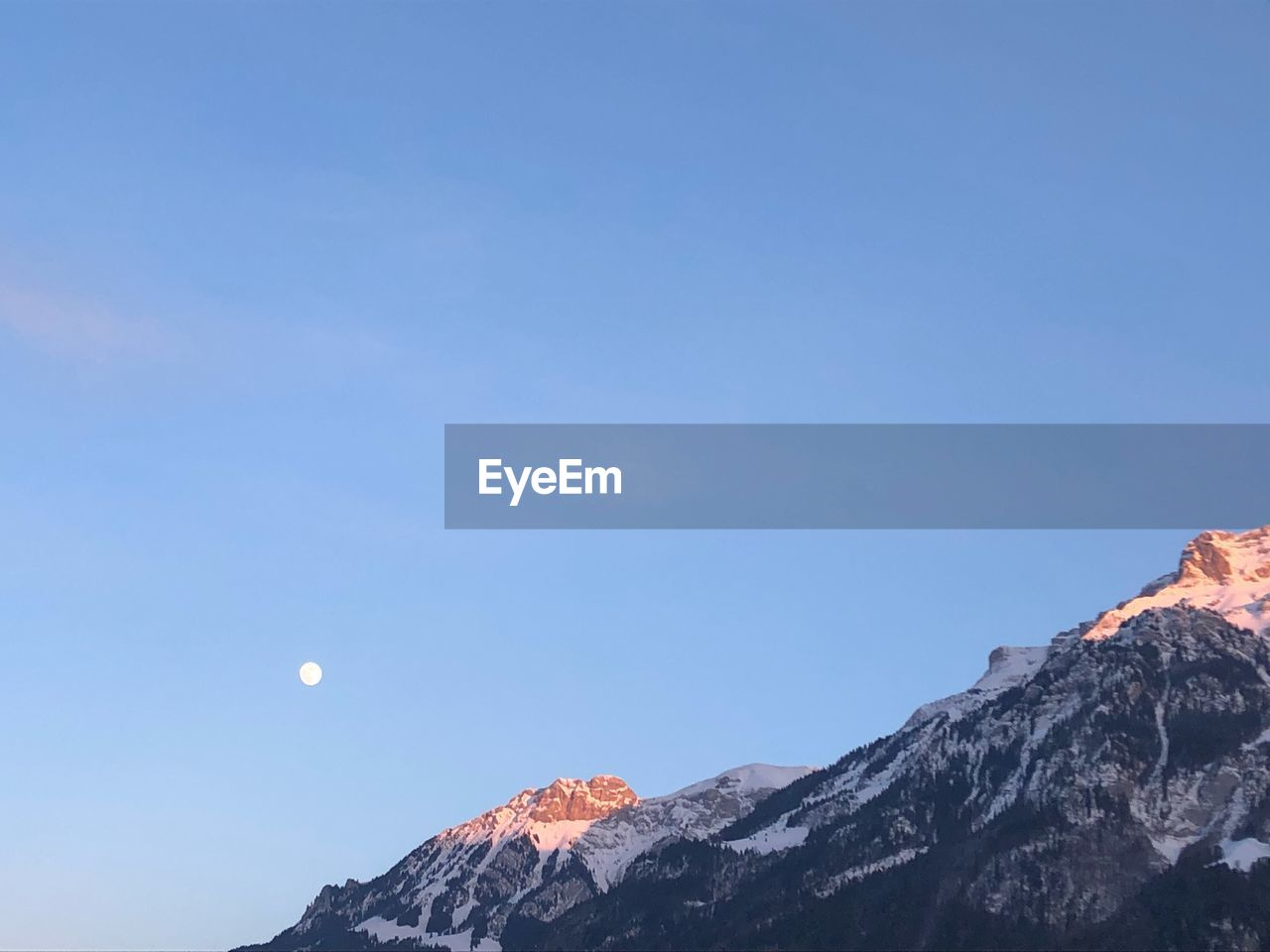 sky, mountain, scenics - nature, moon, beauty in nature, tranquil scene, clear sky, copy space, blue, tranquility, nature, non-urban scene, snow, cold temperature, mountain range, winter, low angle view, no people, idyllic, mountain peak, snowcapped mountain, outdoors, astronomy, formation
