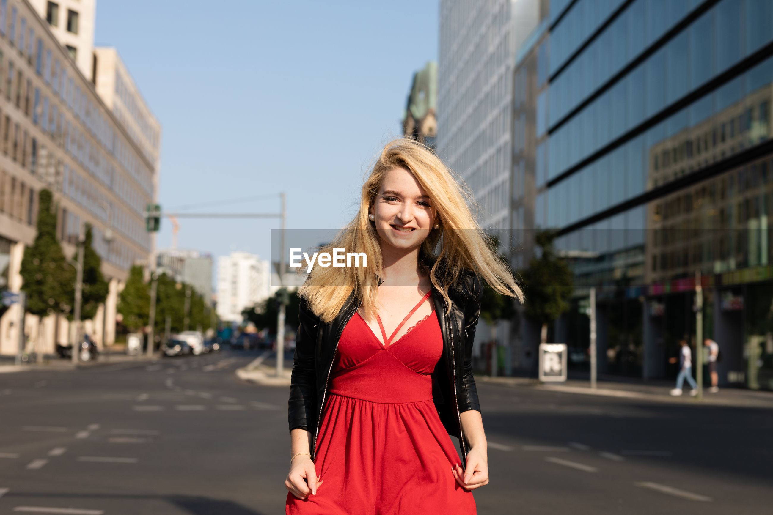 Portrait of smiling young woman standing on road in city