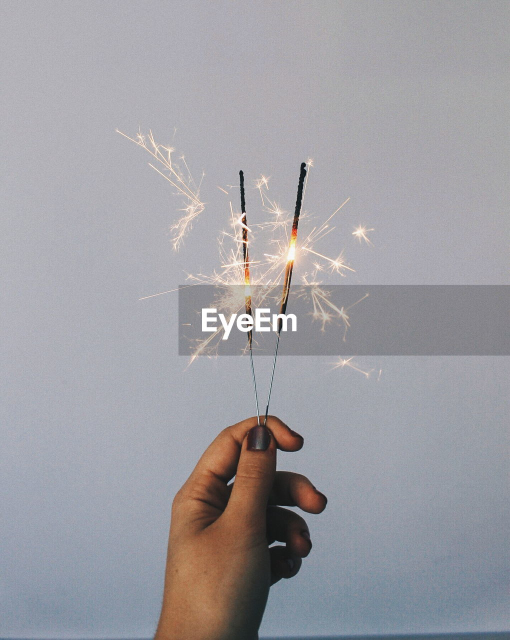 Cropped hand of woman holding sparklers against sky
