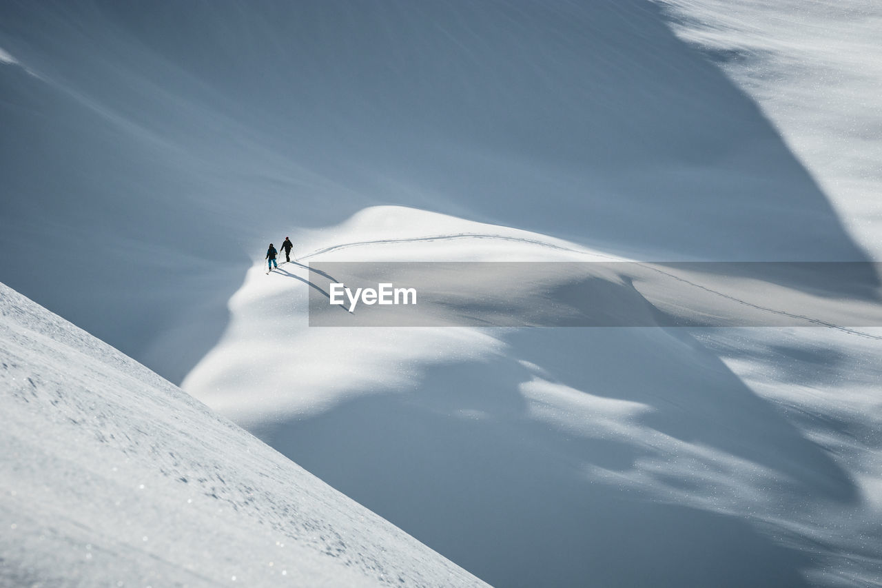 Silhouette of two skiers ski touring in the backcountry of the alps in lienz, austria.