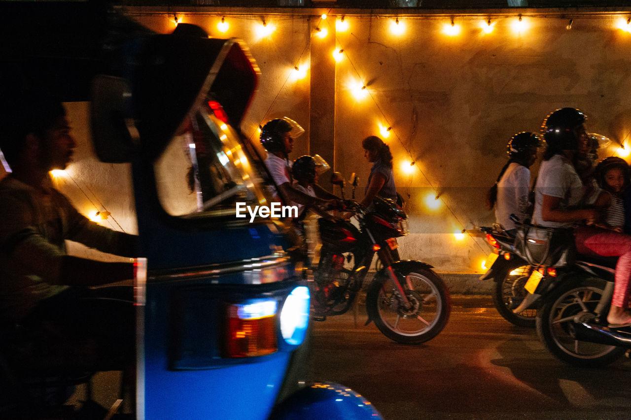 mode of transportation, transportation, illuminated, night, land vehicle, city, street, real people, group of people, motorcycle, men, people, road, travel, rickshaw, motor vehicle, car, bicycle, group, outdoors