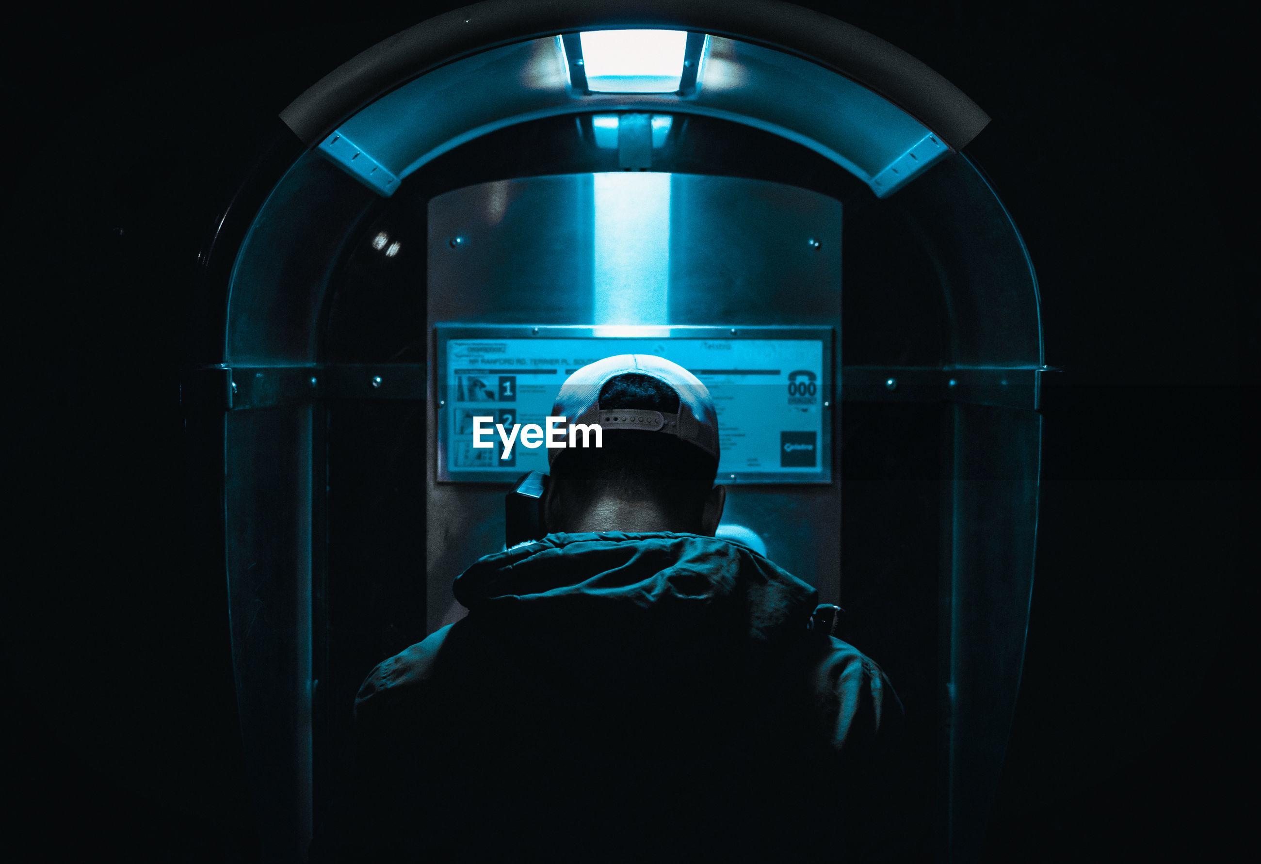 Rear view of man using pay phone at night