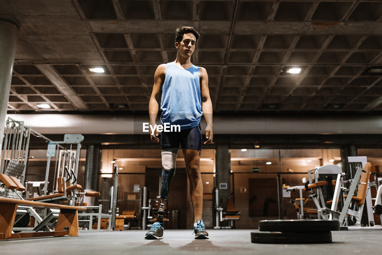 Man with artificial leg standing in gym