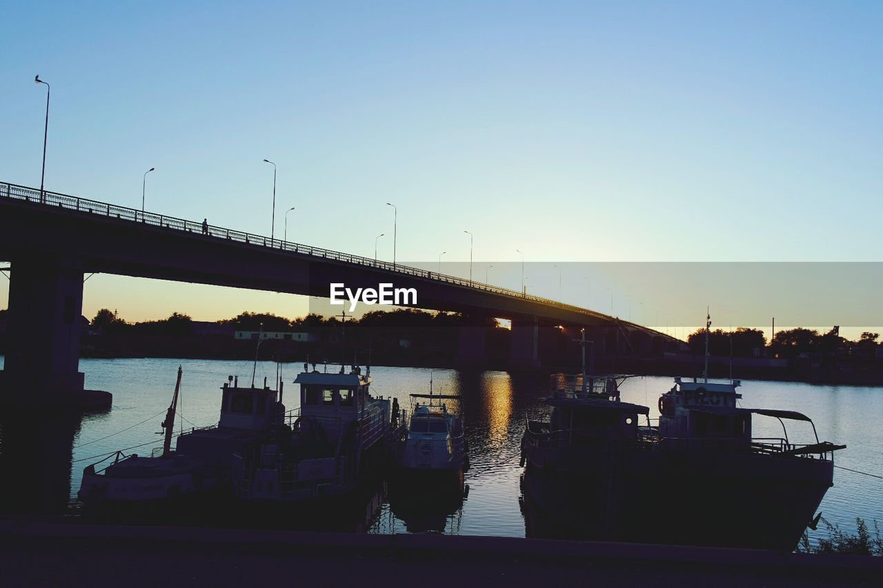transportation, sky, water, nautical vessel, bridge, mode of transportation, sunset, connection, bridge - man made structure, nature, clear sky, built structure, river, architecture, no people, silhouette, outdoors, ship, passenger craft