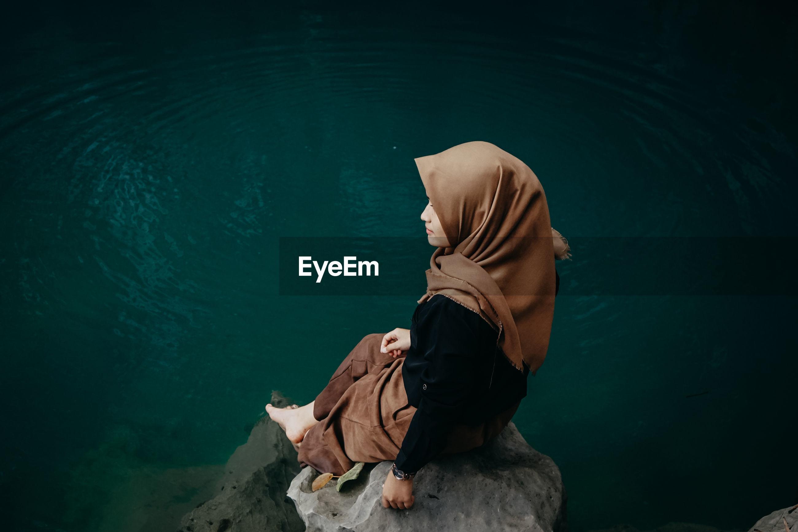High angle view of woman wearing hijab sitting on rock by lake