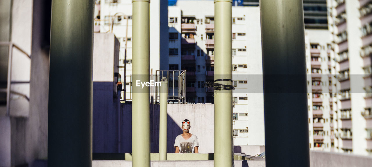 Man On Building Terrace Seen Through Poles