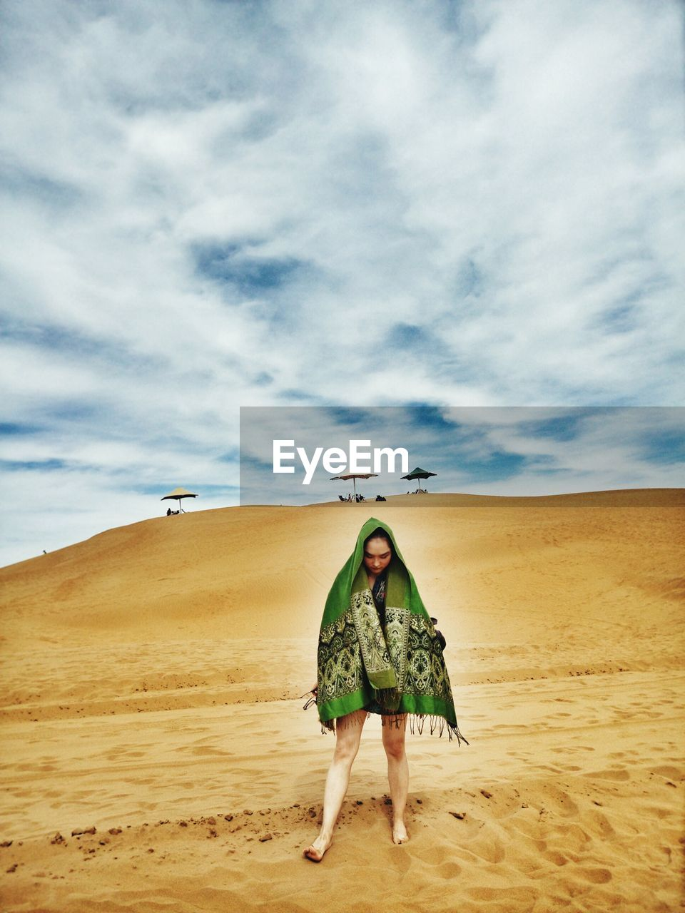 Full length of woman wrapped in shawl standing on sand at beach against cloudy sky