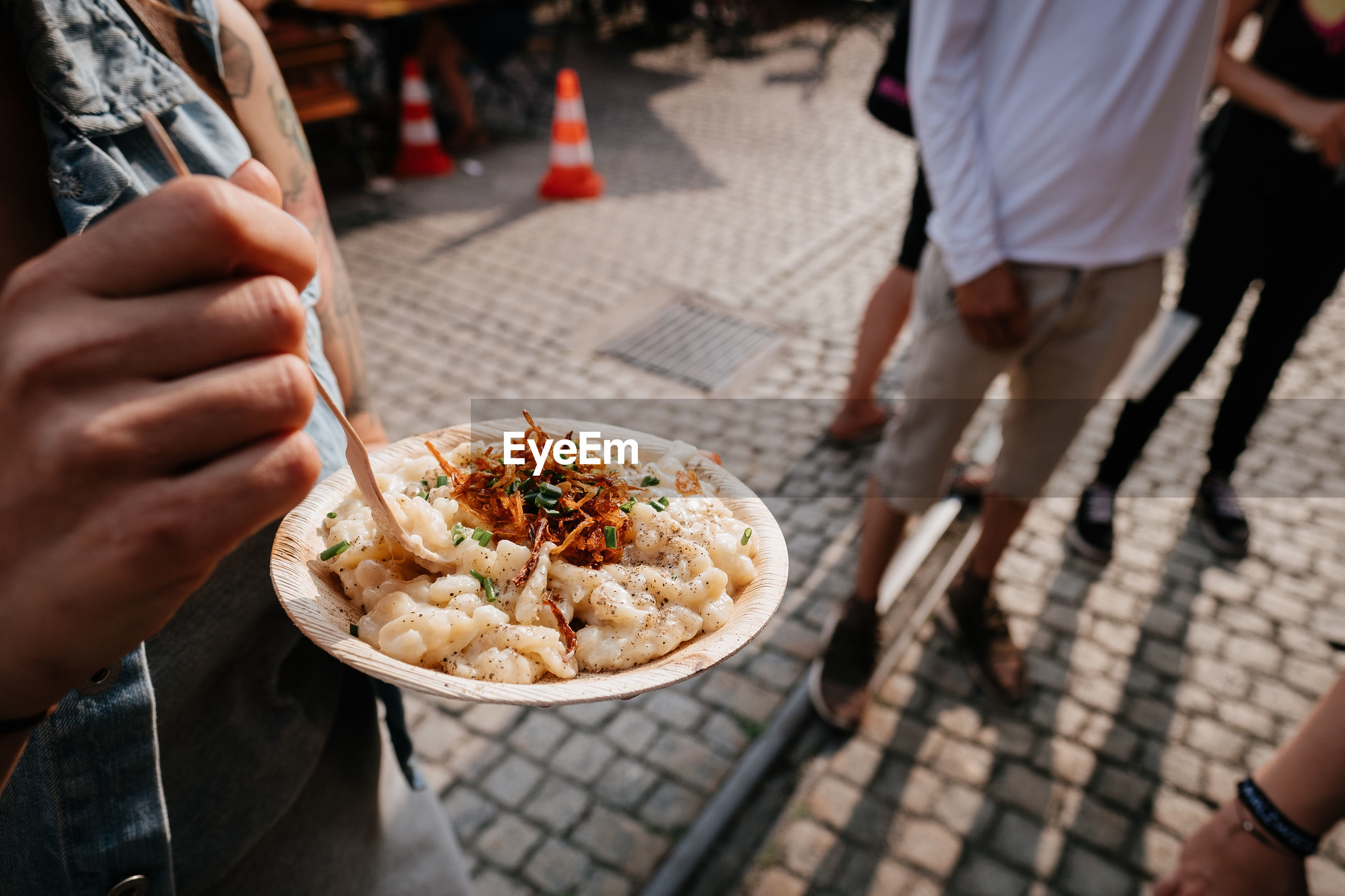 Midsection of woman eating food on street