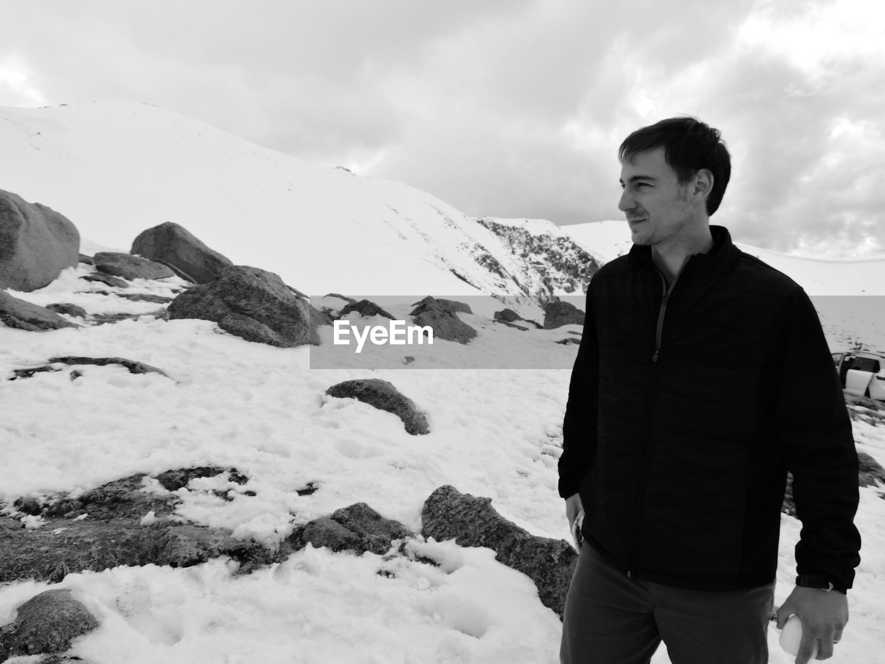 Young Man Standing On Snowcapped Mountain Against Sky