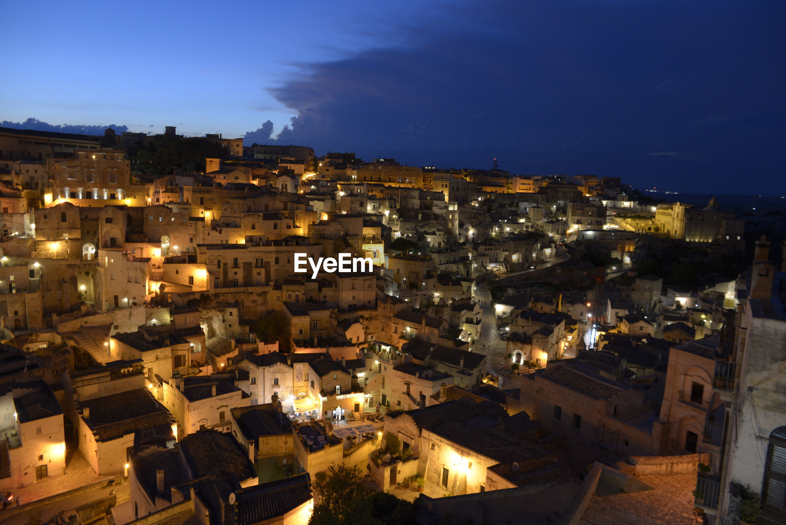 HIGH ANGLE VIEW OF ILLUMINATED TOWNSCAPE AGAINST SKY