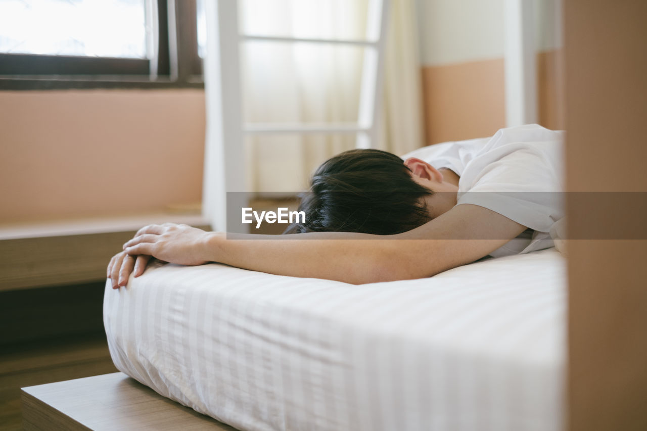 Man lying on bed at home