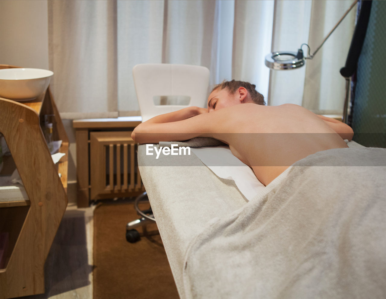 MIDSECTION OF MAN SITTING IN A ROOM