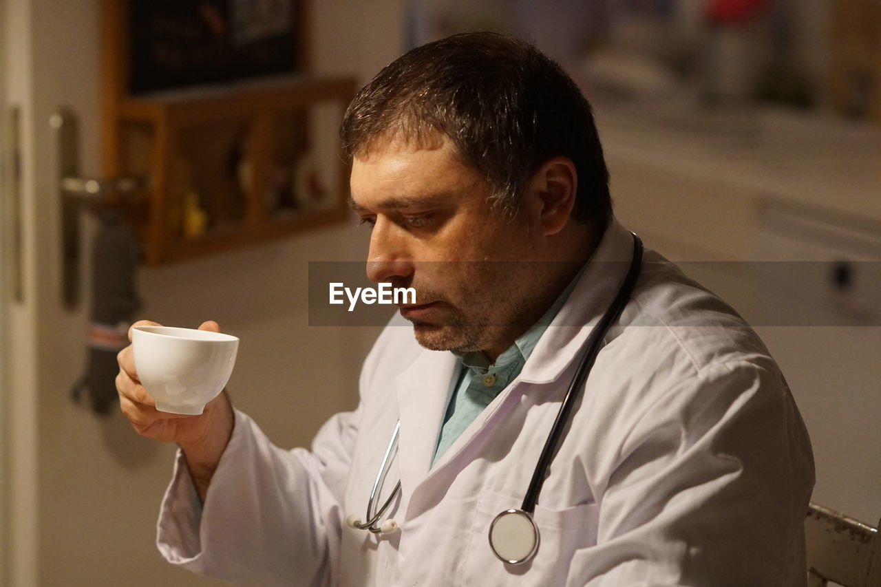 Side View Of Thoughtful Mature Doctor With Coffee Sitting In Hospital