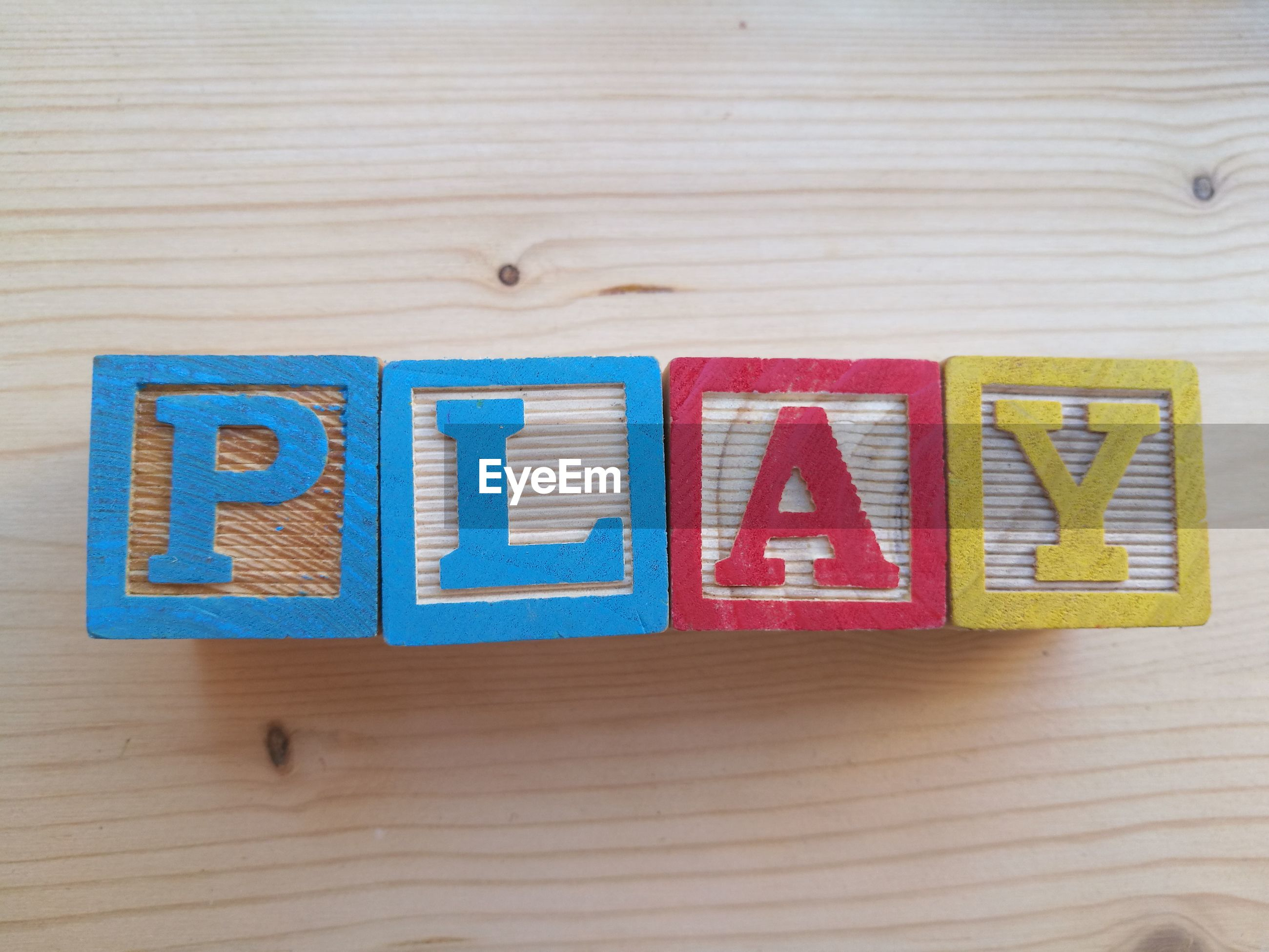 High angle view of toy blocks with text on wooden table