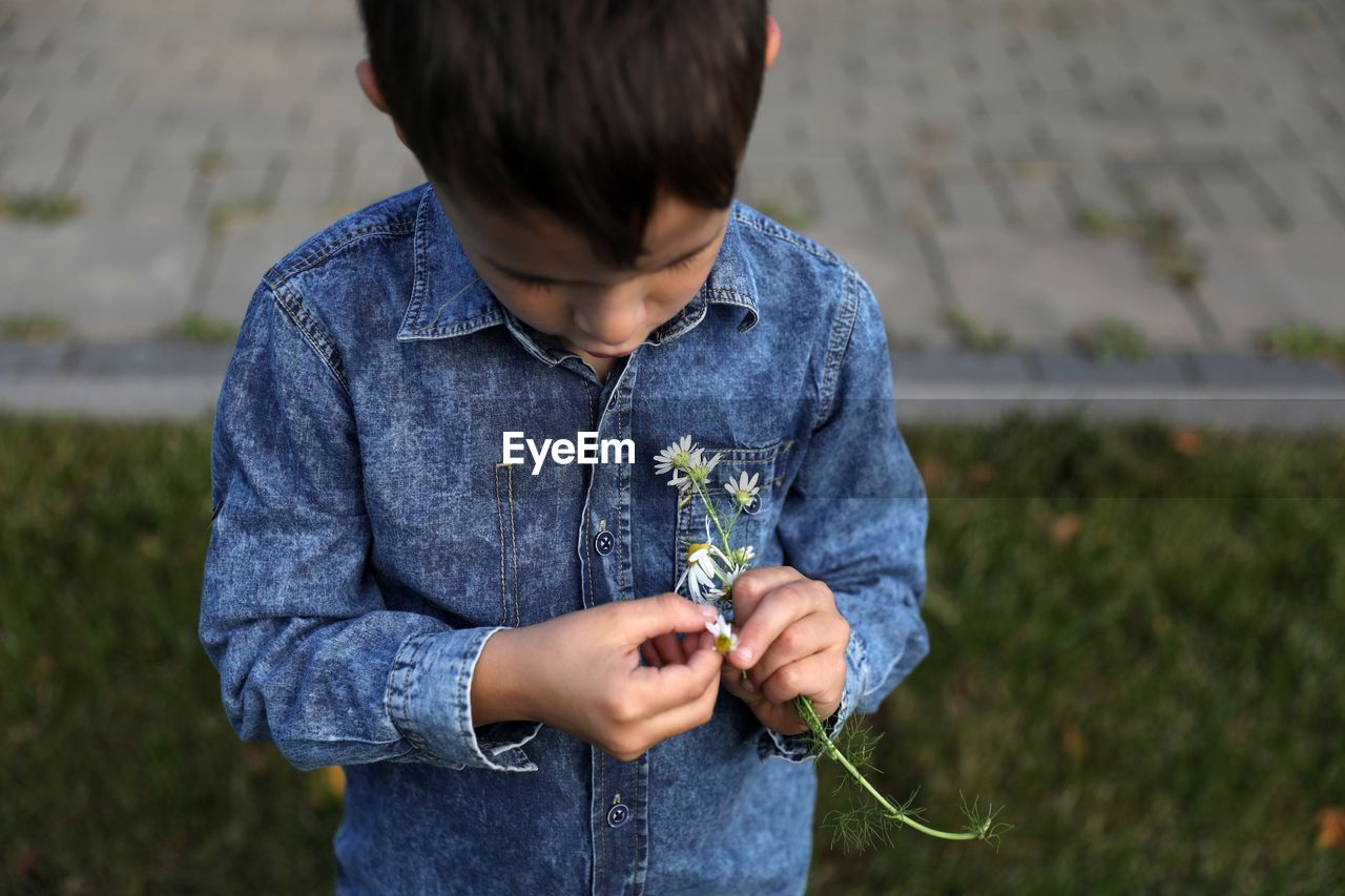 Boy Holding Flower While Standing Outdoors