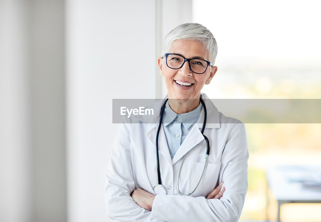 occupation, medical supplies, healthcare and medicine, stethoscope, portrait, looking at camera, medical instrument, smiling, doctor, eyeglasses, clothing, medical equipment, glasses, indoors, one person, lab coat, front view, adult, expertise, waist up, responsibility