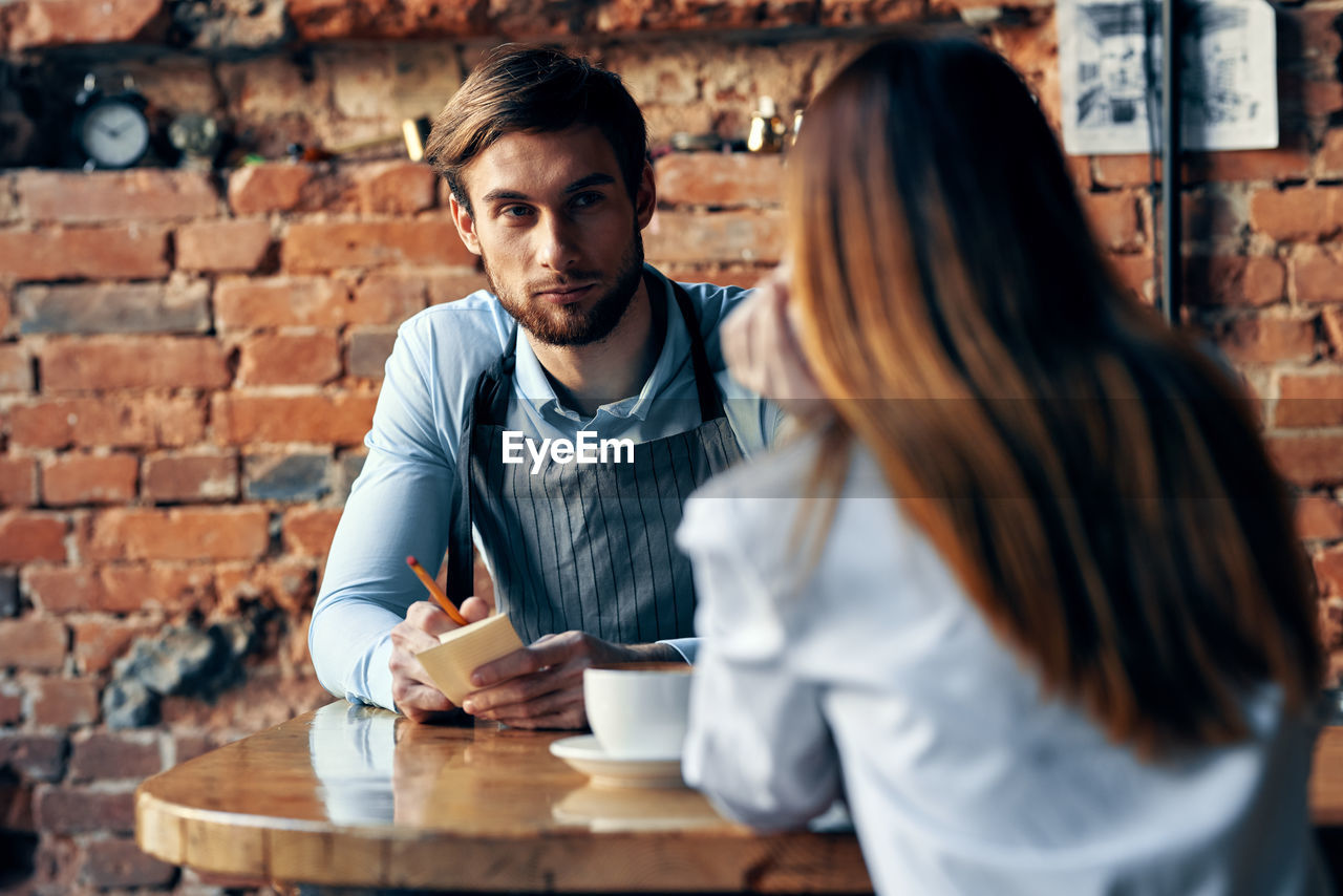 Young couple sitting on table at cafe