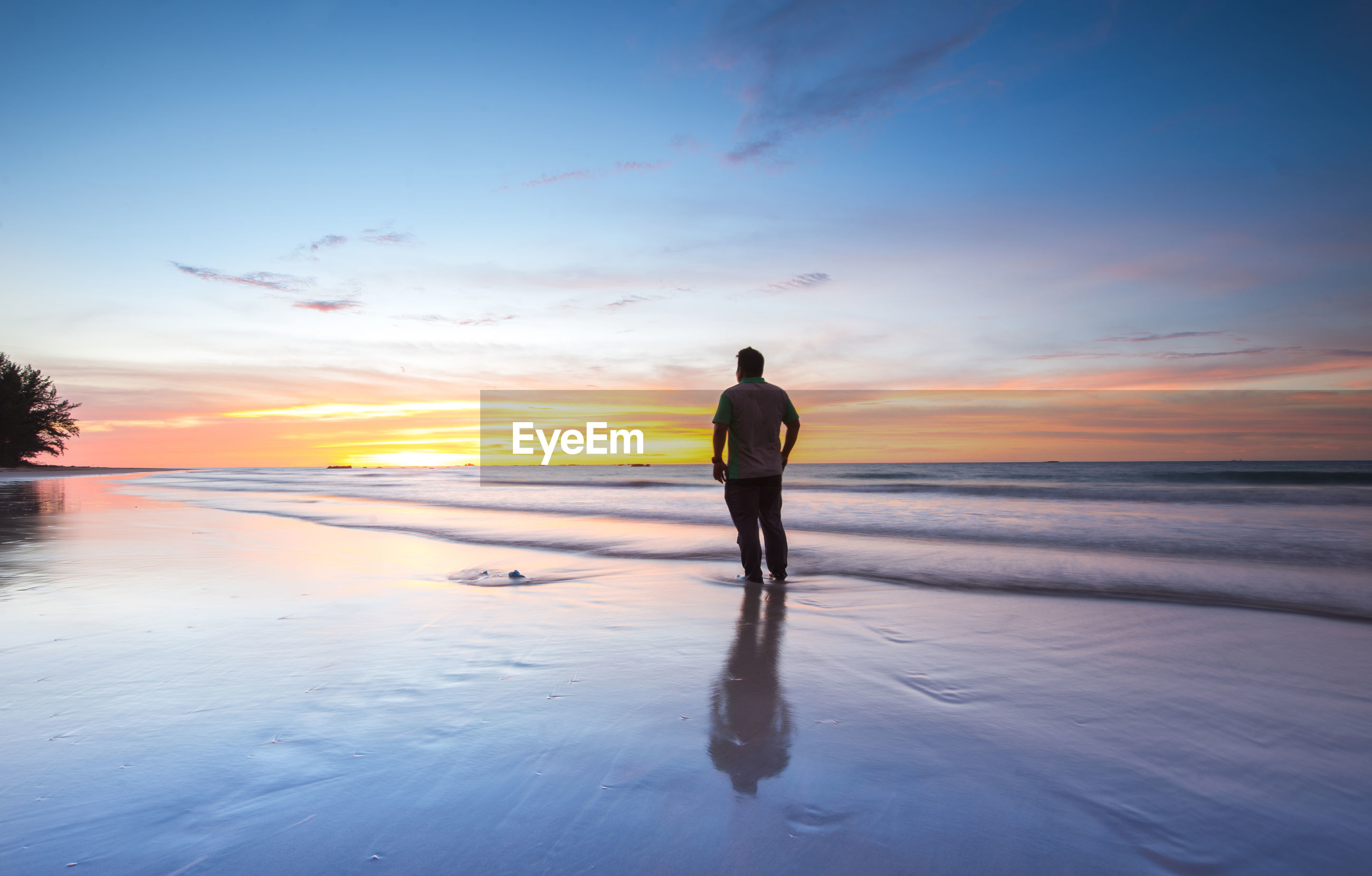 Man standing on shore against sea during sunset