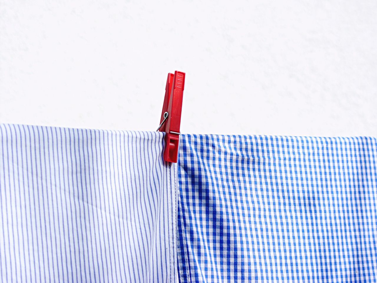 Clothespin on clothesline against white wall