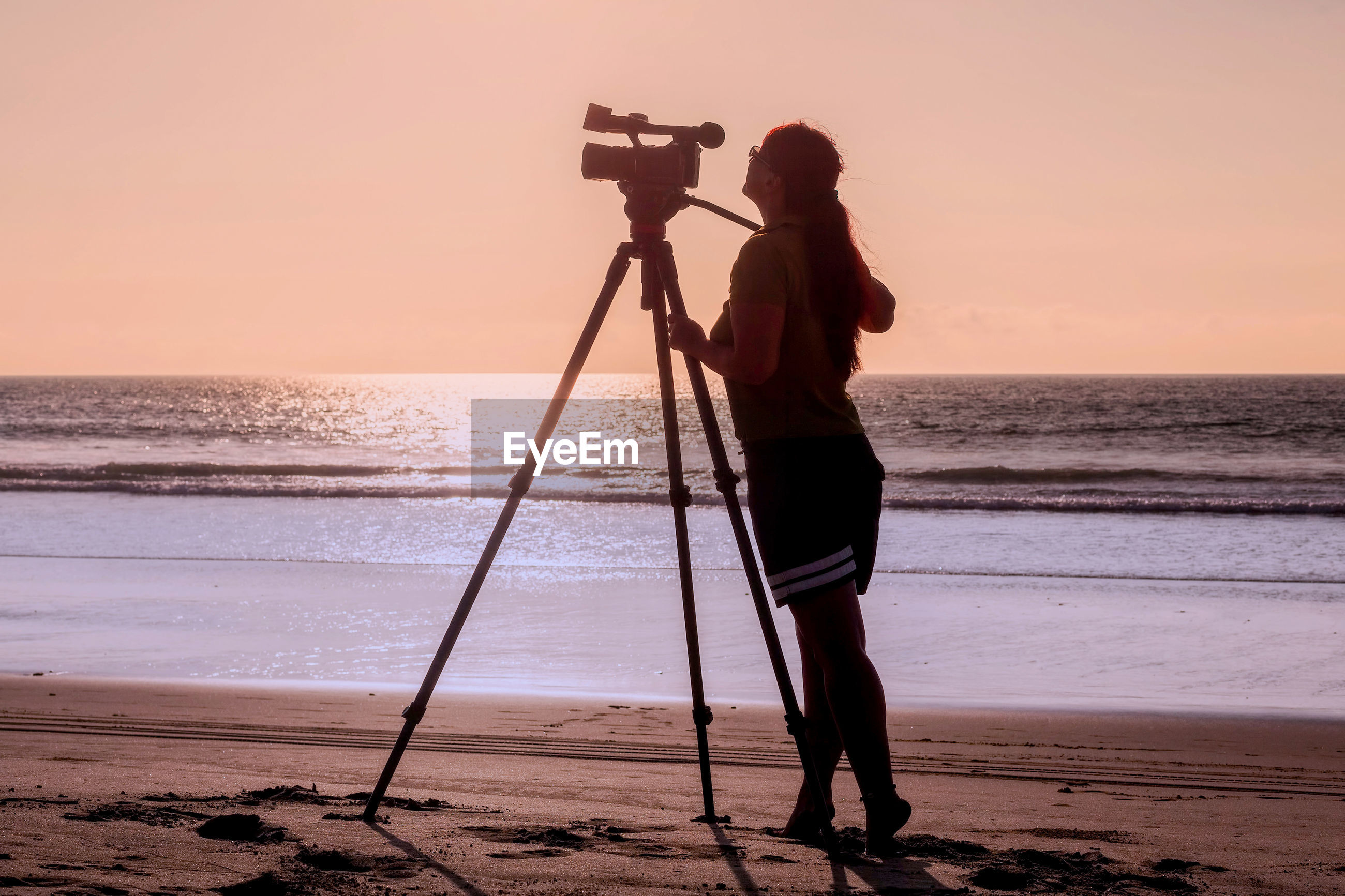 Side view of woman standing with movie camera on tripod at beach