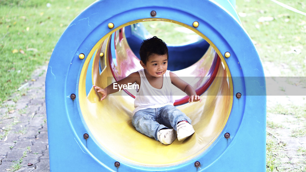 childhood, child, boys, playground, leisure activity, playing, one person, outdoor play equipment, casual clothing, males, enjoyment, real people, front view, day, lifestyles, park, fun, full length, innocence, outdoors, jungle gym