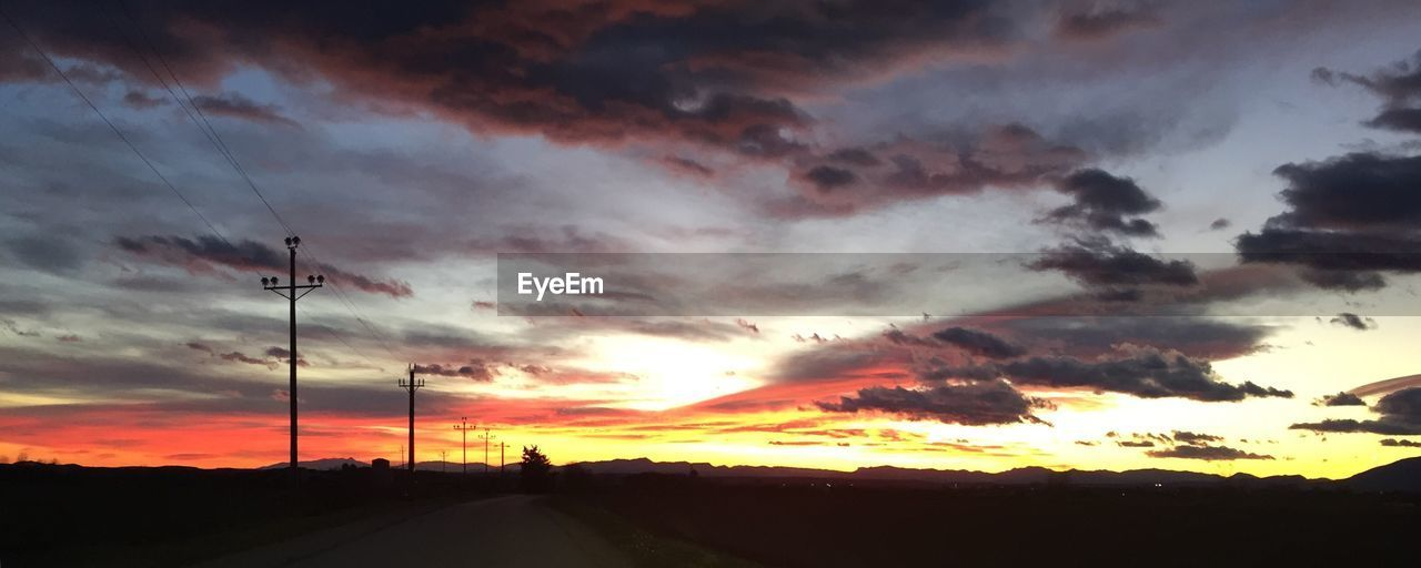 sunset, silhouette, cloud - sky, sky, orange color, dramatic sky, tranquil scene, scenics, no people, beauty in nature, nature, tranquility, cable, outdoors, landscape, road, electricity pylon, telephone line, day
