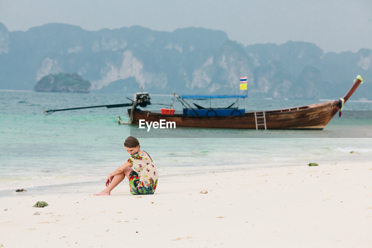 Thoughtful Woman Sitting On Sea Shore By Moored Longtail Boat At Beach