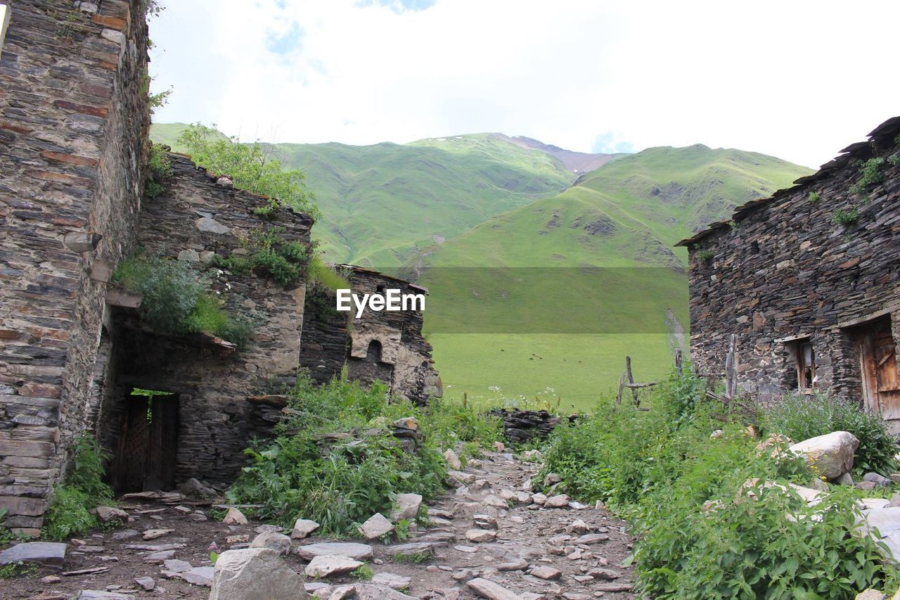 architecture, mountain, built structure, plant, sky, day, nature, tree, no people, green color, scenics - nature, tranquility, building exterior, beauty in nature, tranquil scene, direction, building, history, landscape, growth, stone wall, outdoors, ancient civilization, ruined