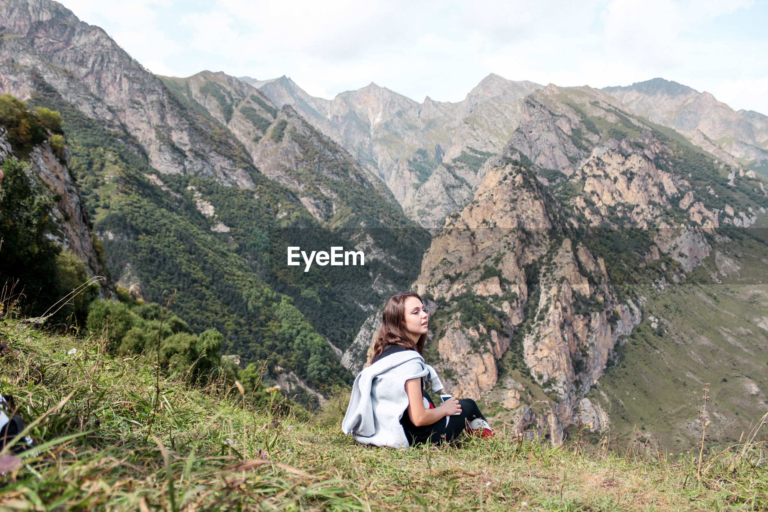Young woman sitting against mountain range