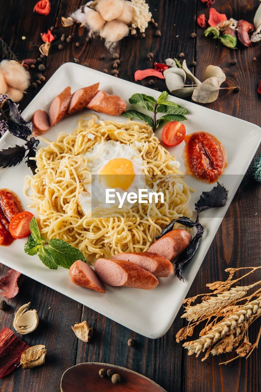 food and drink, food, freshness, table, ready-to-eat, italian food, indoors, egg, healthy eating, vegetable, pasta, serving size, tomato, wellbeing, high angle view, close-up, plate, meal, still life, kitchen utensil, no people, herb, fried egg, egg yolk, breakfast, spaghetti, crockery