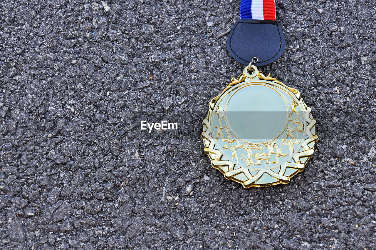 High angle view of gold medal on footpath