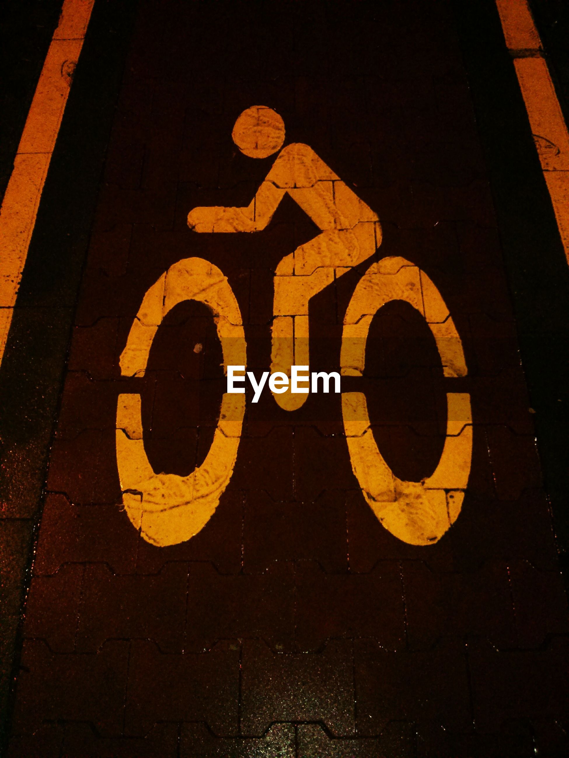High angle view of bicycle lane sign on street at night