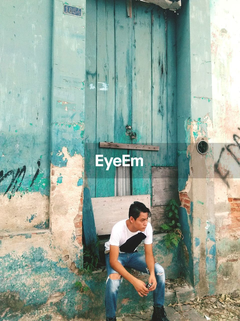Man Looking Away While Sitting By Abandoned Door