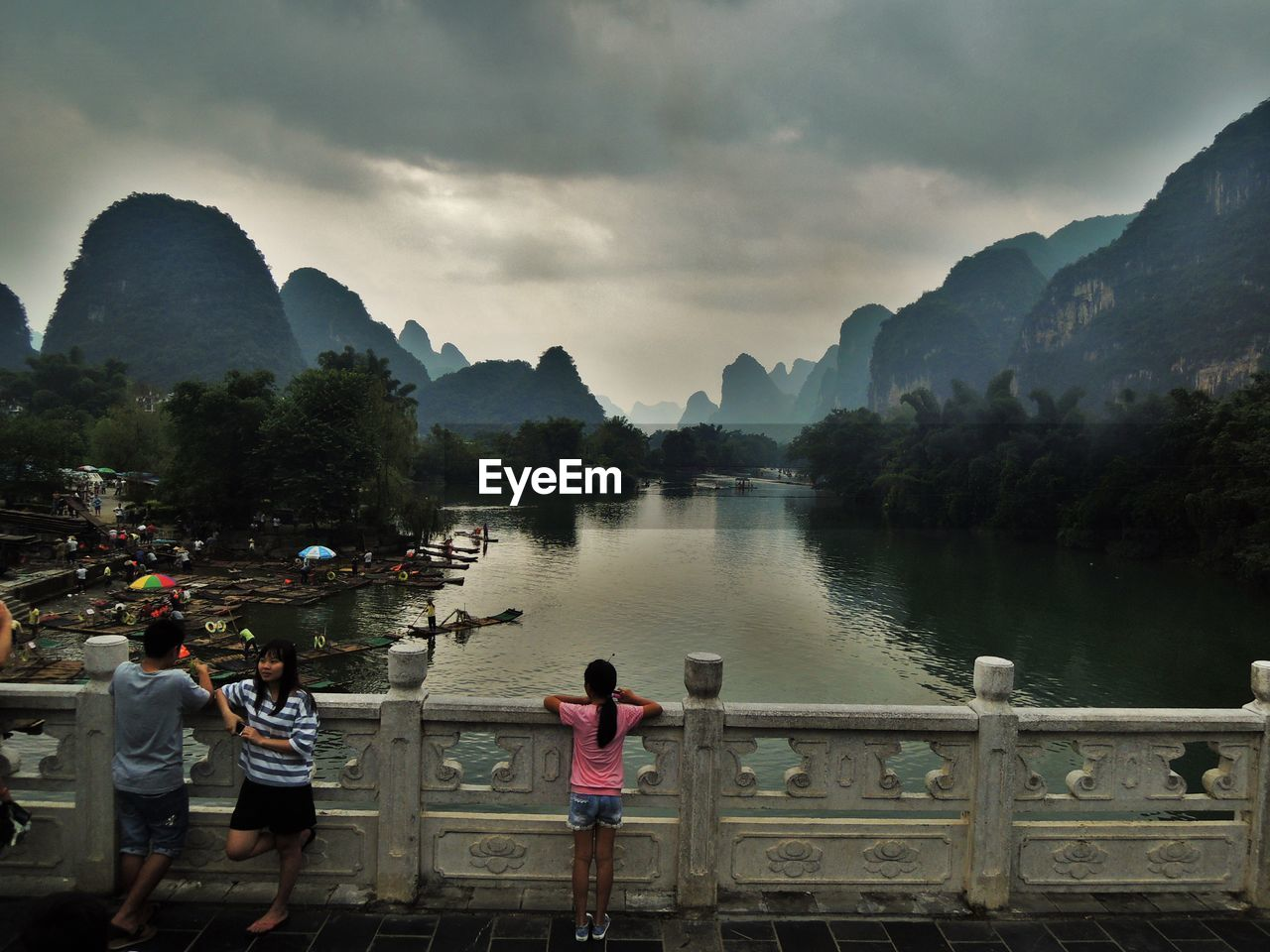 PEOPLE LOOKING AT LAKE AGAINST MOUNTAIN
