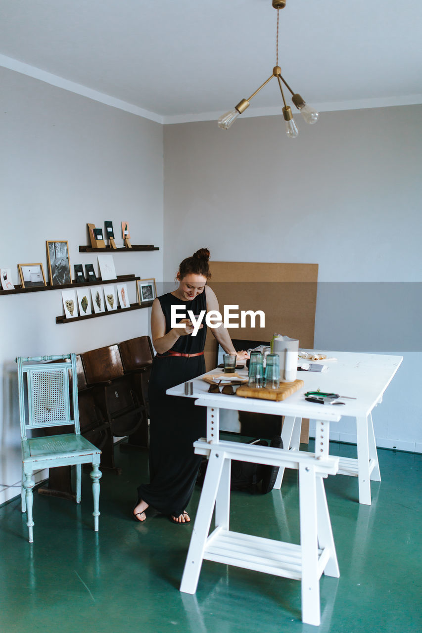 Woman Using Mobile Phone While Standing At Home