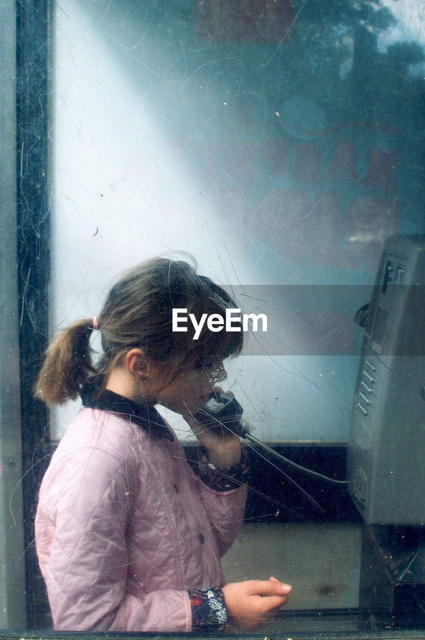 Girl standing in telephone booth