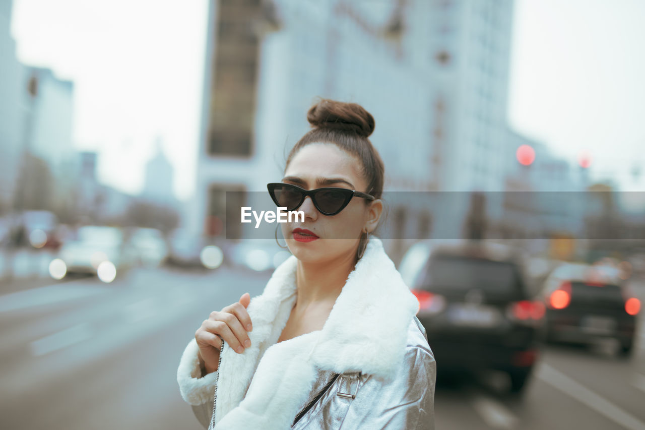 city, focus on foreground, architecture, young adult, one person, street, lifestyles, transportation, young women, beautiful woman, car, waist up, motor vehicle, adult, city life, real people, standing, built structure, fashion, outdoors, hairstyle